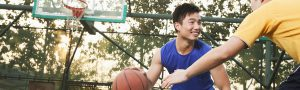 A man smiling and playing basketball