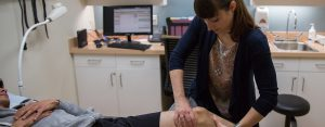 A medical professional working on a patient's knee